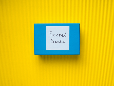 Closed Blue gift box with Secret Santa card on yellow background