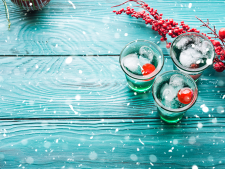 Christmas party green alcohol drinks with cherry. Festive aperitif shots and ornaments on wooden dark table. Holiday background with falling snow