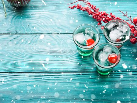 Groene de alcoholdranken van de Kerstmispartij met kers. Feestelijke aperitiefschoten en ornamenten op houten donkere tafel. Vakantieachtergrond met dalende sneeuw