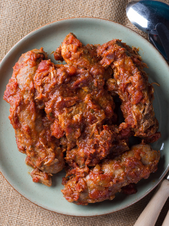 Sausages and pork pullet cooked in traditional Italian tomato ragu sauce. Dish on burlap with cutlery.