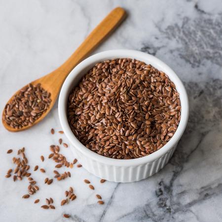 Flax seeds in white ramekin on marble board Stock Photo