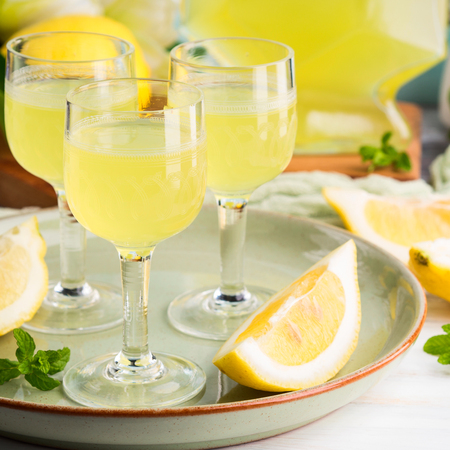 Home made limoncello served in stemmed glasses. Summer still life Stock Photo - 101340083