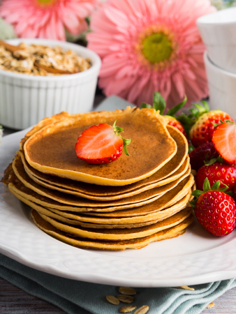Stack of oatmeal flour pancakes with strawberries on white dish