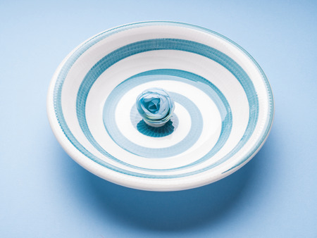 Blue pastel ceramic dish with hypnotizing spiral. Abstract food, tableware crockery concept