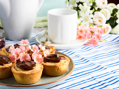 Cakes with frangipane, cherry jam and chocolate frosting. Romantic table setting with flowers. Mothers day card