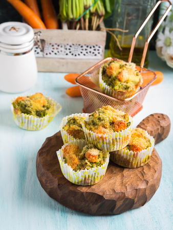 Home made healthy vegetable muffins with carrots and broccoli on wooden board. Corn breading