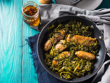 Italian sausages with rapini broccoli in a skillet with table setting on green wooden table