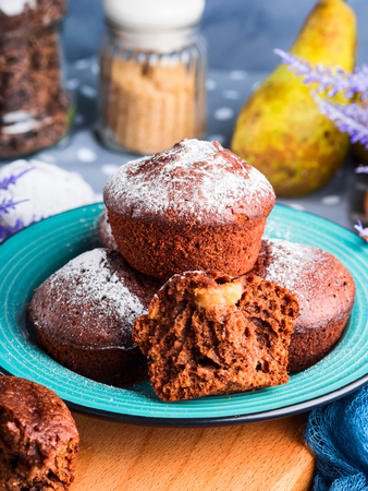 Chocolate home made baked muffins with pears and icing sugar on winter background