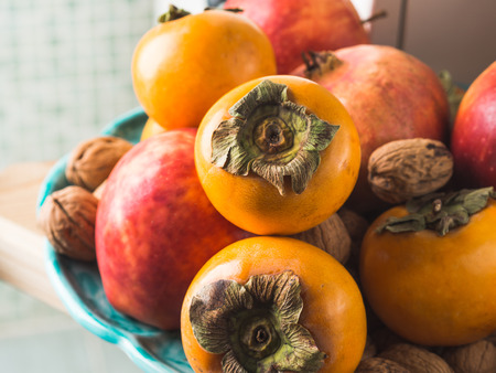 Autumn fresh fruit food persimmons, pomegranate, apples, nuts, in the kitchen on a dish