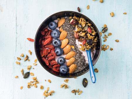 Yogurt raspberry smoothie bowl with goji berries and blueberries, almonds, chia seeds and granola on pastel turquoise wooden background. Plant based breakfast Stockfoto