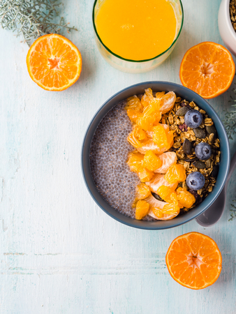 Chia pudding with tangerines and matcha tea granola in a bowl on pastel turquoise wooden background. Plant based breakfast