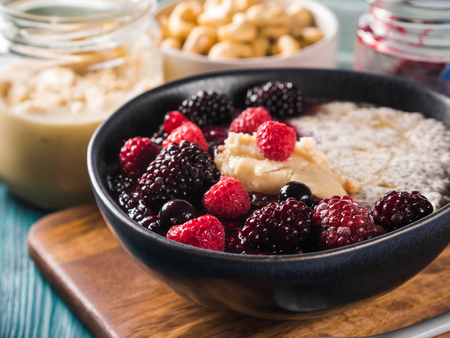 Vegan cashew milk Chia pudding with berries and home made almond butter served in a bowl on wooden board