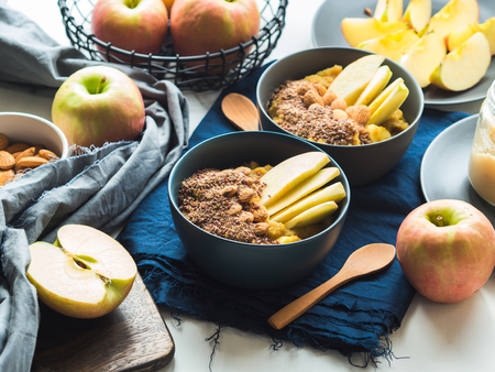 Cozy morning concept with turmeric amaranth porridge served with apples, flax seeds and almonds. Healthy plant based vegan breakfast. Flat lay Archivio Fotografico