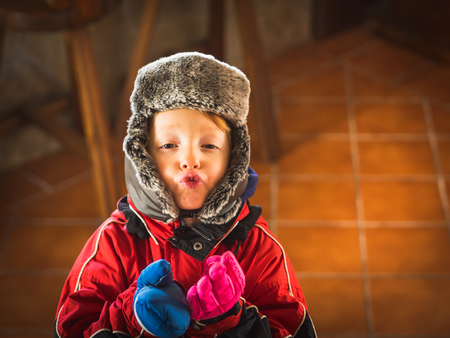 Little 5-year-old boy in snowsuit and cap with earflaps making funny face expressions with different mittens 스톡 콘텐츠