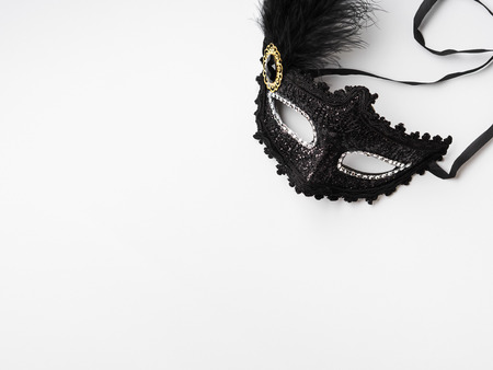 Black carnival mask with feather on white background Stock Photo