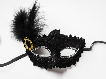 Black carnival mask with feather on white background Imagens