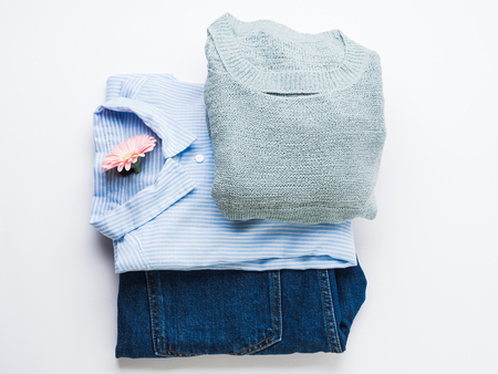 Folded female clothes jeans, shirt, sweater on white. Fashion flat lay. Woman mothers day concept