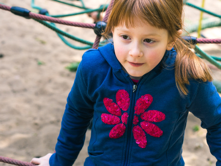 Little 9-year old redhead girl playing on playground