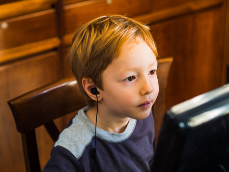 Cute little blonde boy playing or studying at computer with headset very concentrated Фото со стока