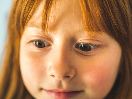 Cute redhead little girl. Funny expression. Vivid eyes and cheerful smile Фото со стока