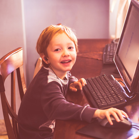 Cute little blonde boy enjoying playing at computer with headset. Toned Фото со стока