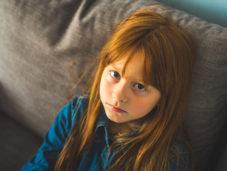 Cute redhead little girl looking at the viewer serious. Фото со стока