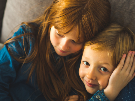 Two blonde sibling kids in blue shirts on a sofa hugging. Portrait of happy cute children indoors. Closeup Фото со стока