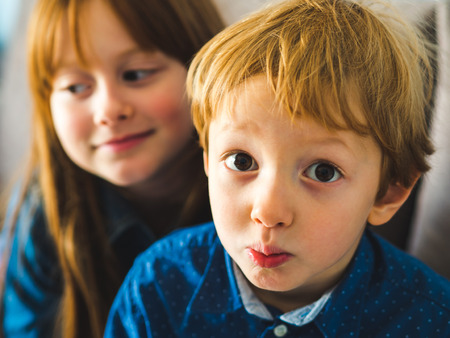 Two blonde cute sibling kids in blue shirts making funny expressions. Portrait indoors