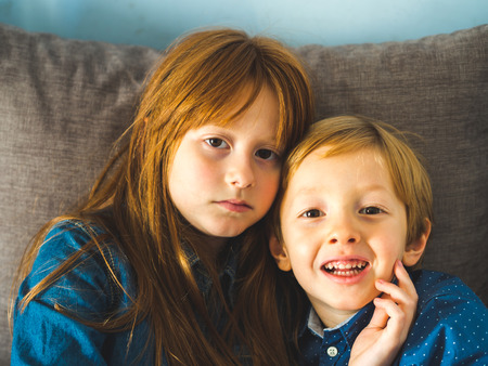 Two blonde sibling kids in blue shirts on a sofa hugging. Portrait of children indoors Фото со стока