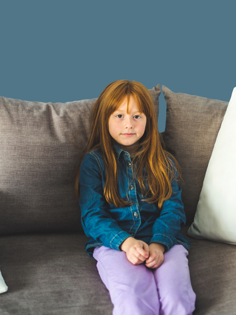 Cute redhead little girl looking at the viewer and smiling calmly, sitting on gray couch