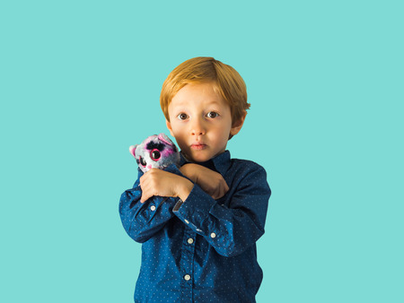 Little blonde boy isolated on blue holding a soft toy in hands. Sad or surprised expression Фото со стока