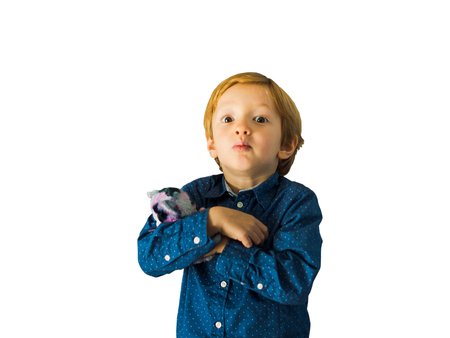 Little cute blonde boy isolated on white holding a toy and looking at us with funny expression Фото со стока