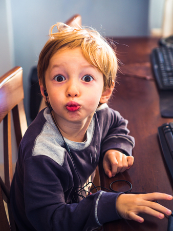 Cute little blonde boy playing at computer with headset. Funny expression