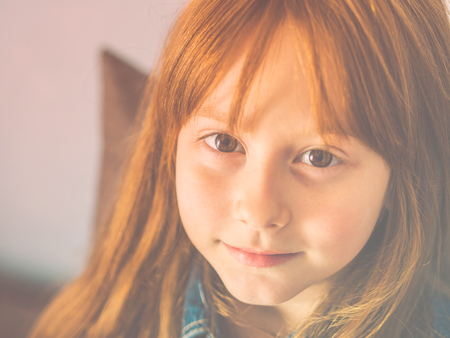 Cute redhead little girl looking at the viewer and smiling. Vivid eyes and cheerful smile. Toned