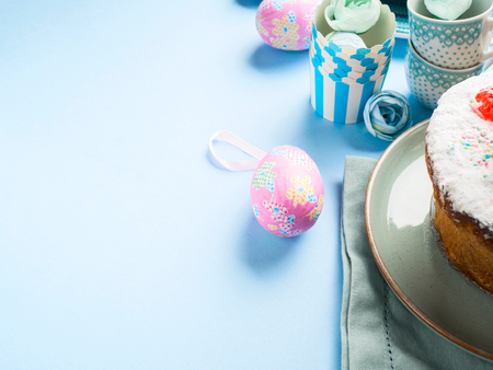 Easter concept background with cake and decor eggs on minimal blue