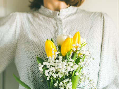 Woman holding bouquet of tulips. Womans mothers day. Flowers for Valentines day. Spring Easter symbol
