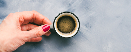 Cup of coffee in womans hand with red manicure on sky blue painted background. Minimal flat lay Фото со стока
