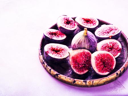 Plat de figues violettes sur fond de pierre. Ton néon violet