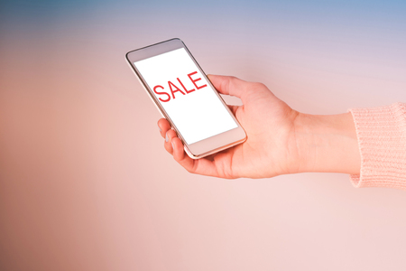 Womans hand with mobile phone screen with word Sale. Pink and blue duotone background.