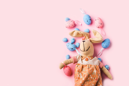 Colorful decor easter eggs and bunny on pastel pink background. Flat lay