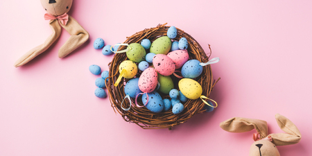 Colorful decor easter eggs in a nest and bunnies on pastel pink background. Flat lay