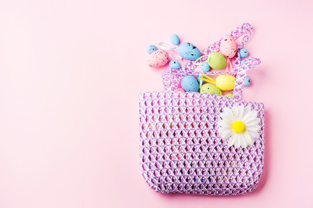 Colorful decor easter eggs from a pink spring bag on pastel background. Spring holiday flat lay
