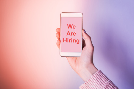 Womans hand with mobile phone screen on pink and violet purple abstract background. We are hiring wrtitten on the screen
