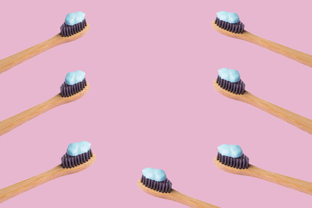 Frame of bamboo toothbrushes with blue toothpaste isolated on lilac pink background. Personal dental hygiene concept. Zero waste