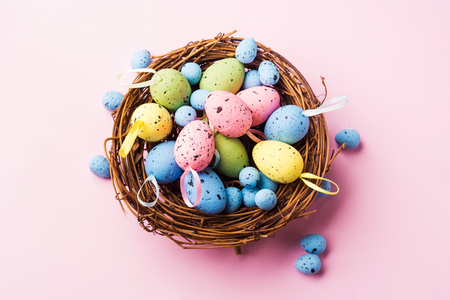 Colorful decor easter eggs in a nest on pastel pink background. Flat lay