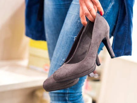 Woman wearing jeans, trying high heels in a fast fashion store.