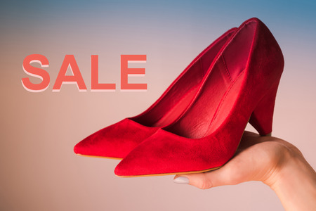 Woman holding red high heels on hand on blue and pink background with word Sale. Shopping concept
