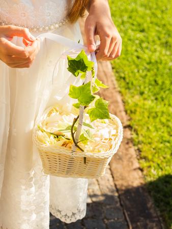 Flower girl in white dress holding basket of rose petals in the church garden