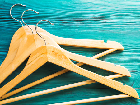 Wooden hangers with no clothes on green wooden background. Clothing storage, sale shopping concept