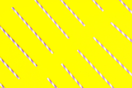 Purple paper straws on bright yellow color background. Pattern